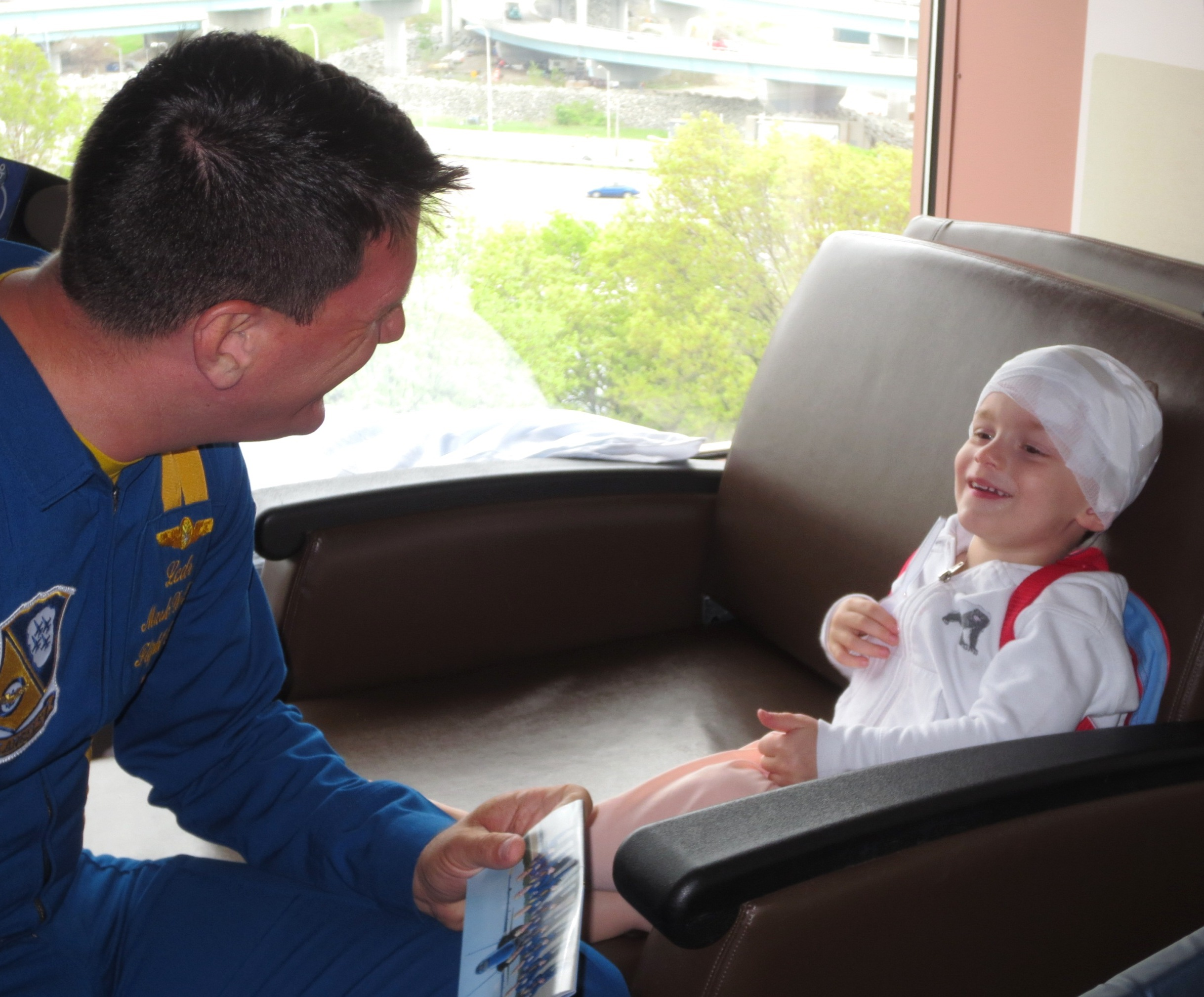 Sharing a Smile: Mark DeBuse, MD, Lt. Commander, U.S. Navy Flight Surgeon and Blue Angels pilot enjoys a moment with Connor Urban during his visit to Hasbro Children's Hospital on Friday, May 16.